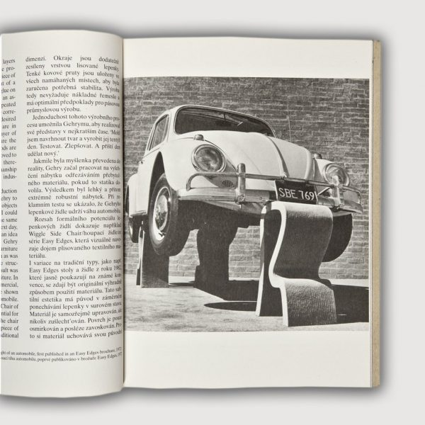Volkswagen Beetle supported on all four wheels with cardboard side chairs
